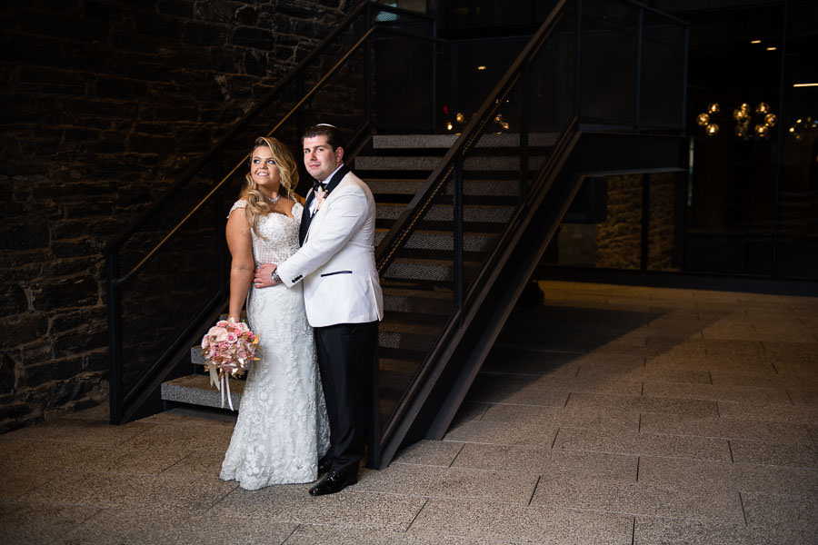 bride and groom pose for their wedding photo session in dumbo brooklyn