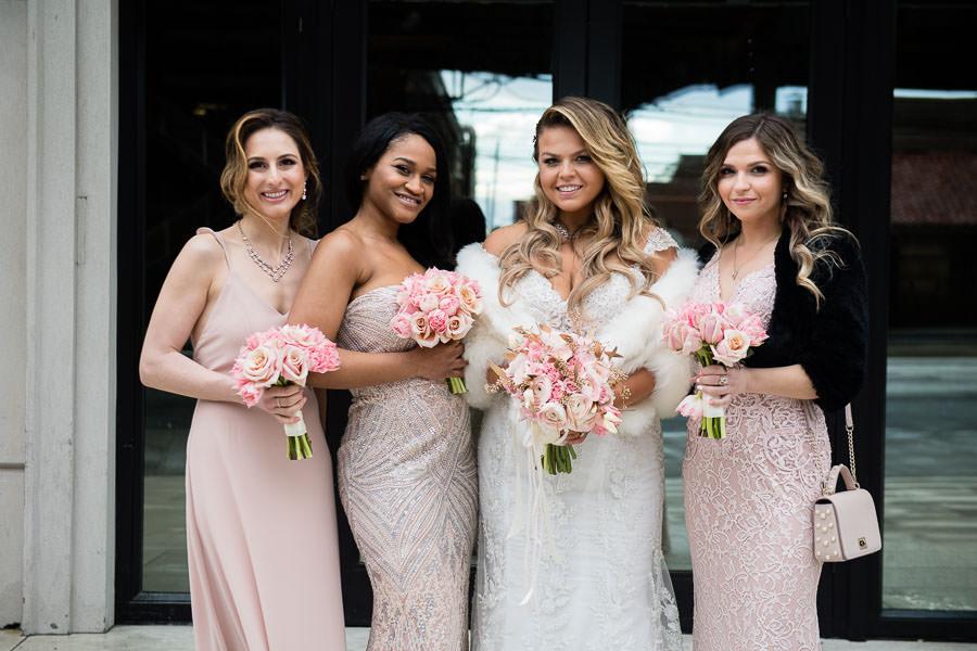 bride and bridesmaids laugh in front of metropolitan ballroom