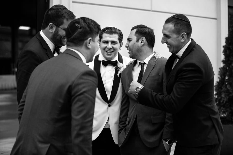 groom and groomsmen candid moment as they laugh