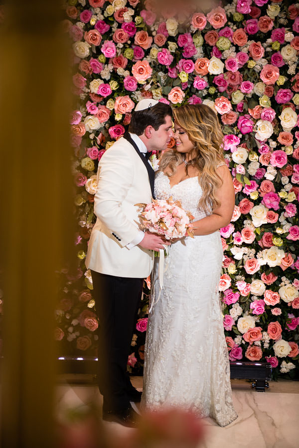 bride and groom posing in front of flower wall by  Gary Abramov Event Productions DBA Floral Art