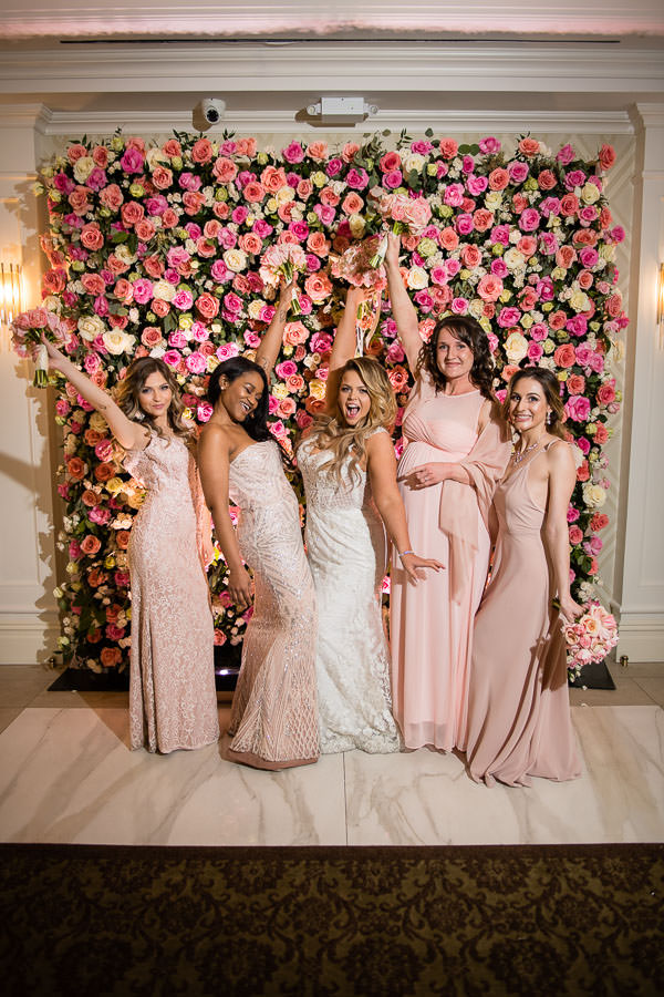 bride and bridesmaids posing in front of flower wall by  Gary Abramov Event Productions DBA Floral Art
