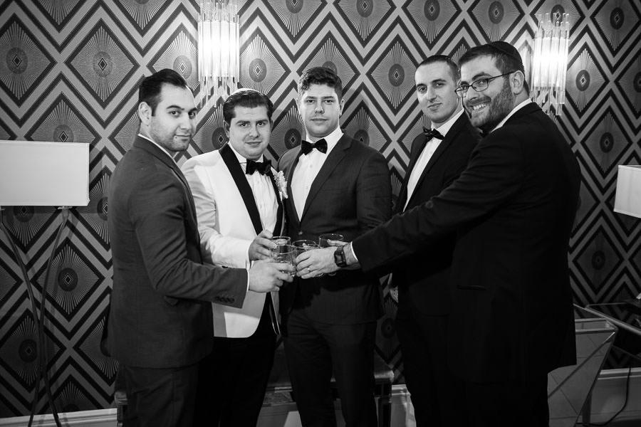 groom and groomsmen drinking whiskey before wedding