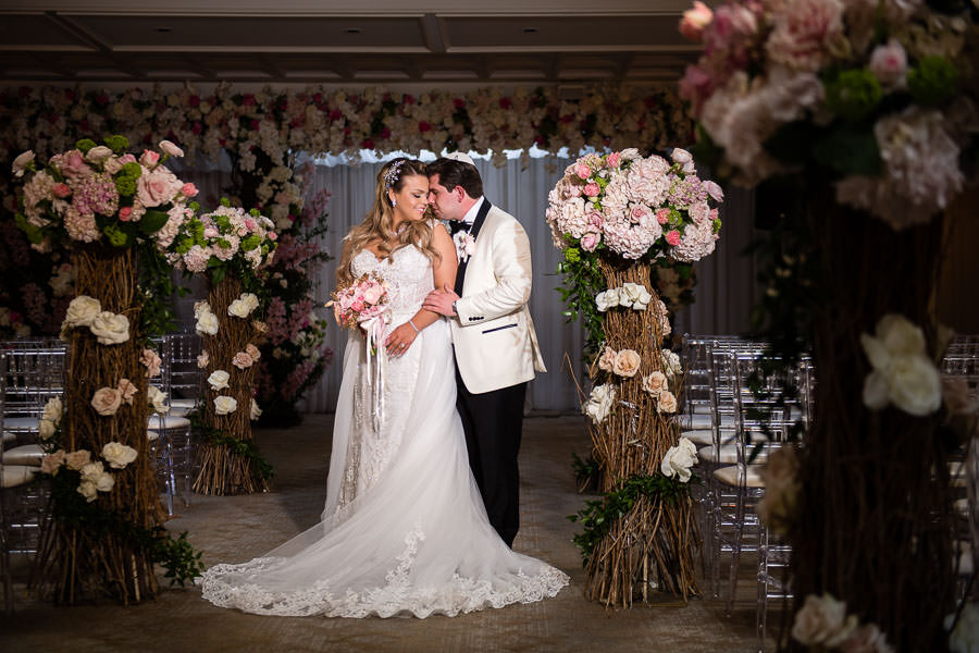 bride and groom surrounded by flowers at their wedding metropolitan ballroom