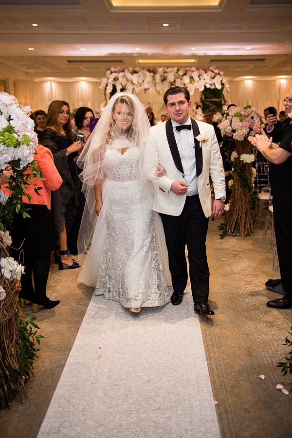 bride and groom walk down the aisle at metropolitan ballroom
