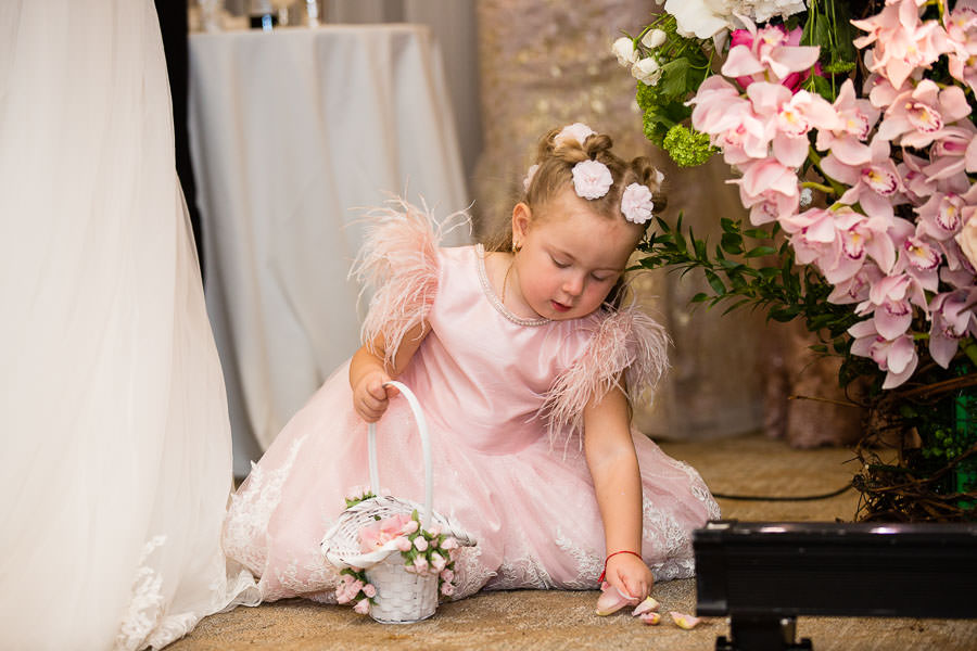 flower girl picks up petals during wedding ceremony