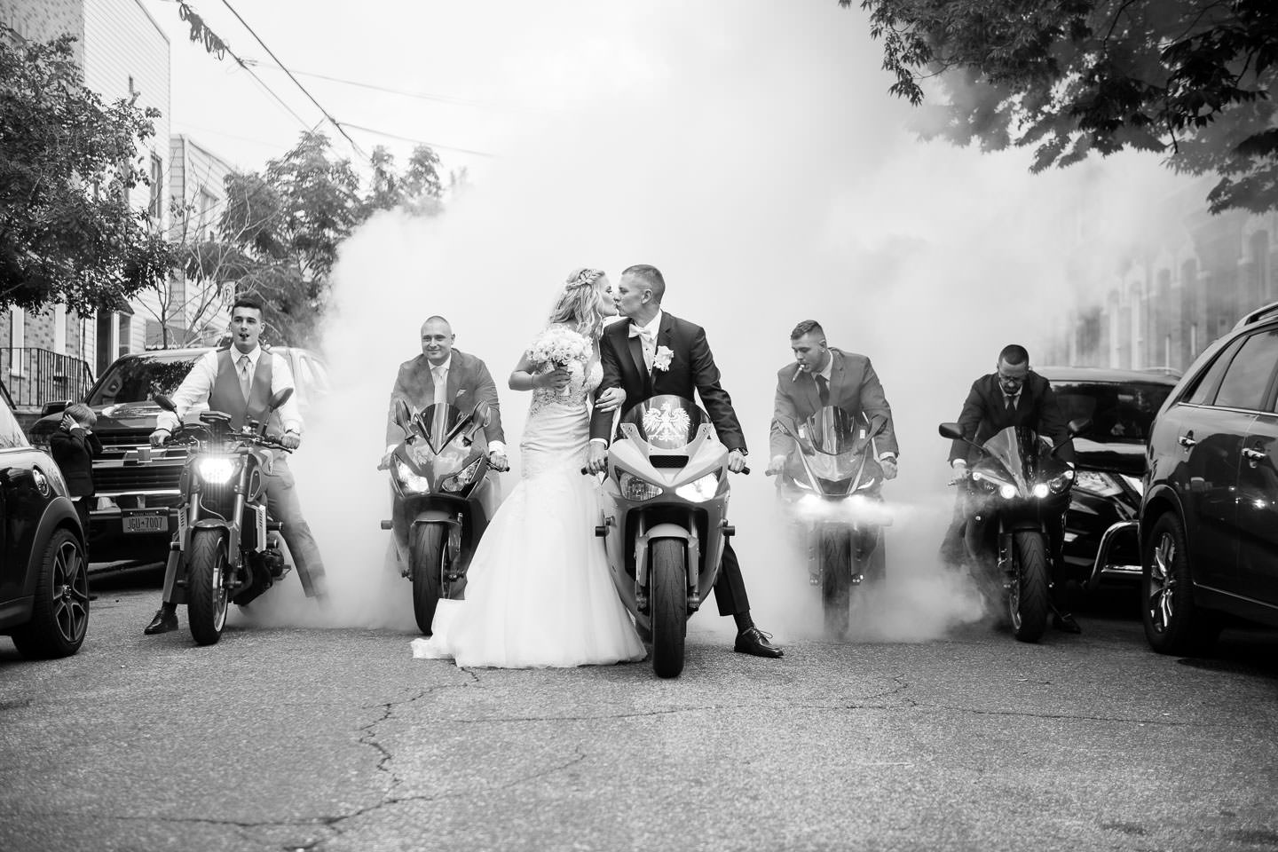 bride and groom pose with motorcycle while groomsmen do burnouts before wedding