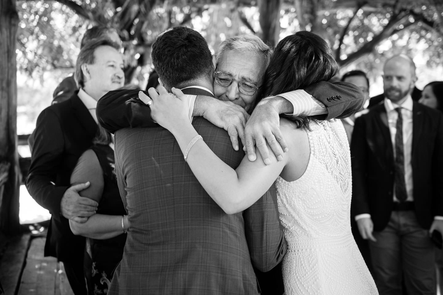 father of groom hugs bride and groom at wedding ceremony very emotional